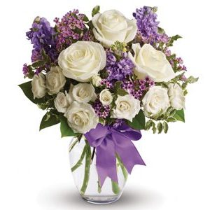 Thia vase of flowers is made up of mauve, purple and white flowers.