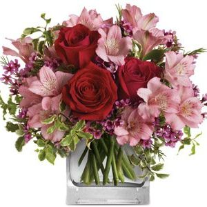 A glass cube of roses alstromeria and pink filler flowers surrounded by green foliage.