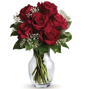 Six long stem premium red roses presented in a vase for love and for roamce with some sweet white filler flower and greenery.
