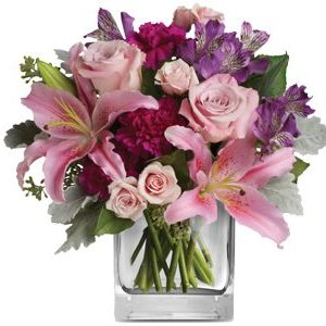 A modern glass cube collection of Oriental Lilies, pink Roses, long lasting Carnations and hints of lavender Alstromeria.